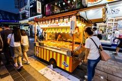 Сувон, Южная Корея - 14-ое июня 2017: Ожидание женщины поставщика покупателей в ее киоске фаст-фуда на главной улице в Сувоне Еда стоковые изображения