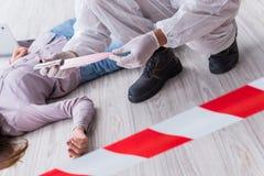 Судебнохимический исследователь на mur женщины места преступления расследуя Стоковые Фото