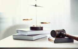 Судит молоток, масштабы правосудия и книги на таблице в комнате Стоковое Изображение