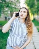 Сужения чувства беременной женщины вызывая для помощи стоковая фотография
