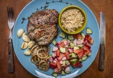 Суккулентные чеснок и лук свинины жаркого sauce салат с луками и травами зажаренными чесноком голубая плита с вилкой и нож на дер Стоковые Фото