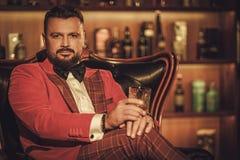 Сумасбродный стильный человек при стекло вискиа сидя на кресле внутри Стоковые Фотографии RF