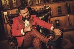 Сумасбродный стильный человек при стекло вискиа сидя на кресле внутри Стоковые Изображения