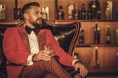 Сумасбродный стильный человек при стекло вискиа сидя на кресле внутри Стоковое Фото