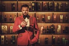 Сумасбродный стильный человек с стеклом вискиа в клубе джентльмена Стоковая Фотография