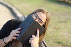 Сумасшедшая белокурая девушка со стеклами смотря к вам и держа книгу стоковая фотография