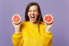 Сумасшедшая кричащая молодая женщина в свитере меха держа halfs свежего зрелого грейпфрута изолированного на фиолетовой пастельно стоковое изображение