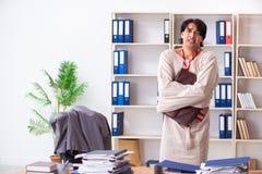 Сумасшедший молодой человек в смирительной рубашке на офисе стоковое изображение rf