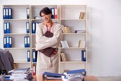 Сумасшедший молодой человек в смирительной рубашке на офисе стоковое фото
