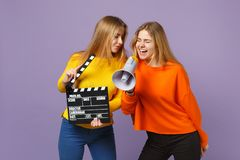 2 сумасшедших молодых белокурых девушки сестер близнецов держа классическое черное clapperboard создания фильма, клекот на мегафо стоковые фотографии rf