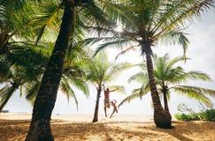 Сумашедше скача futher и сын на сиротливом пляже острова стоковое фото