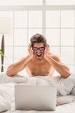 Сумашедший парень кричащий на компьютере в спальне стоковая фотография