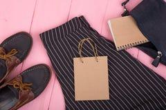 сумка, брюки, ботинки, сумка подарка, блокнот на розовой деревянной предпосылке стоковая фотография rf