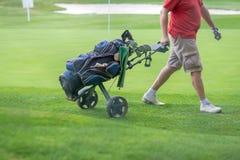 Сумка гольфа тяги человека на trundler стоковые изображения rf
