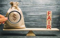 Сумка денег и деревянные блоки с ярмаркой слова Баланс Оценка сходной цены, задолженность денег Честная сделка Умеренная цена Опр стоковое изображение