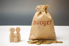 Сумка денег с бюджетом слова стоит около семьи Концепция управления семейный бюджет Выгода и доход Сбережения и стоковое фото rf