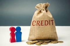 Сумка денег с кредитом и семьей слова Концепция аккумулировать деньги для того чтобы отплатить заем Сохраняя деньги на оплачивать стоковое фото