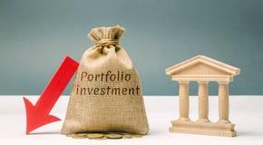 Сумка денег с портфельными инвестициями слова и вниз стрелка около банка Отток депозитов Падение банка стоковое фото rf