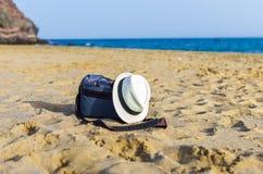 Сумка и белая шляпа на песке пляжа стоковое фото