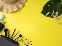 Сумка макияжа с разнообразием предпосылки продуктов красоты желтой стоковое фото