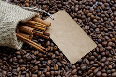 Сумка мешковины с фасолями циннамона и кофе сырцовыми и ярлыком продажи Стоковые Фото