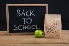 Сумка обеда бумажная, зеленое яблоко и шифер с текстом назад к школе на деревянном столе стоковое изображение