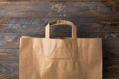 Сумка посещения магазина бакалеи бумаги Брауна kraft на деревянной предпосылке свободные от Пластмасс альтернативы вычеркивают не стоковое фото