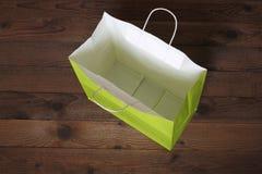 Сумка подарка зеленой книги на деревянной предпосылке Стоковое фото RF