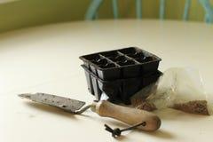 Сумка семян рядом с небольшим лопаткоулавливателем и модулями для начала семени Садовничая концепция засева концепции и весны стоковые фото
