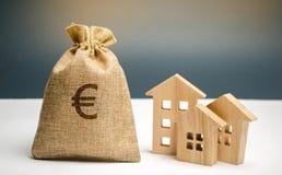 Сумка со знаком денег и евро и деревянными домами Финансировать в стране Инвестировать деньги в недвижимости Сбережения и накопле стоковая фотография