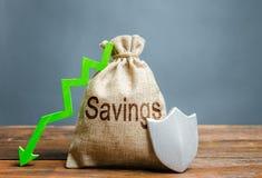 Сумка со сбережениями, экраном и зеленым цветом надписи вниз со стрелки Гарантированная защита личных сбережений, вкладов r стоковые фотографии rf