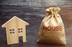Сумка с деньгами и домом слова и деревянным домом Концепция приобретения недвижимости Купите дом, квартиру свойство стоковые фотографии rf
