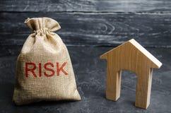 Сумка с деньгами и риском слова и деревянным домом Покупая свойство на кредите Концепция финансового риска Потеря снабжения жилищ стоковое фото