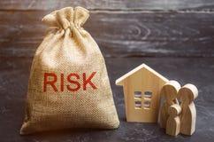 Сумка с деньгами и риском слова и деревянным домом Покупая свойство на кредите Концепция финансового риска Потеря снабжения жилищ стоковое изображение rf