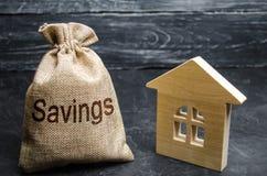 Сумка с деньгами и сбережениями слова и деревянным домом Концепция приобретения недвижимости Купите дом, квартиру свойство стоковое фото