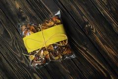 Сумка целлофана с высушенными плодоовощами на темной деревянной предпосылке Стоковое Изображение