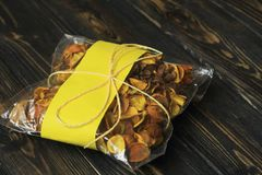 Сумка целлофана с высушенными плодоовощами на темной деревянной предпосылке Стоковые Изображения