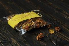 Сумка целлофана с высушенными плодоовощами на темной деревянной предпосылке Стоковые Фотографии RF