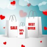 3 сумки белой бумаги с продажей обозначают положение на предпосылке голубого неба с облаками и падать вниз или красными сердцами  Стоковая Фотография RF
