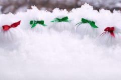 Сумки рождества с красочными смычками с подарками стоят в снеге на предпосылке деревьев стоковые изображения rf