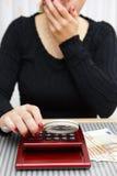 Сумма женщины наблюдая на калькуляторе с лупой стоковая фотография