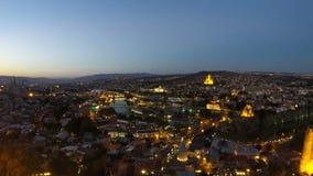 Сумрак понижаясь над большим городом, светами освещая городской пейзаж с горами afar акции видеоматериалы