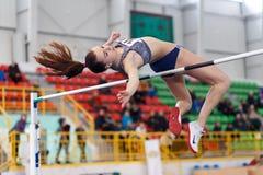 СУМЫ, УКРАИНА - 17-ОЕ ФЕВРАЛЯ 2017: молодая спортсменка скача над баром в конкуренции высокого прыжка квалификации  Стоковое Изображение