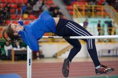 СУМЫ, УКРАИНА - 17-ОЕ ФЕВРАЛЯ 2017: молодая спортсменка скача над баром в конкуренции высокого прыжка квалификации  Стоковые Фото