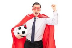 Супергерой веселя и держа футбол Стоковые Изображения RF