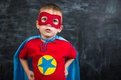 Супергерой мальчика в маске голубой накидки красной и красная футболка с звездой Стоковые Фотографии RF