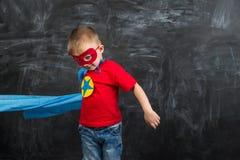 Супергерой мальчика в маске голубой накидки красной и красная футболка с звездой Стоковые Изображения RF