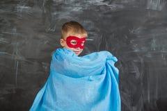Супергерой мальчика в маске голубой накидки красной и красная футболка с звездой Стоковое Изображение