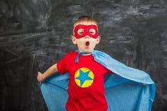 Супергерой мальчика в маске голубой накидки красной и красная футболка с звездой Стоковые Изображения