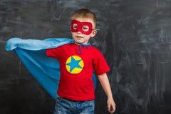 Супергерой мальчика в маске голубой накидки красной и красная футболка с звездой Стоковое фото RF